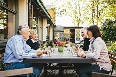 Side view of happy senior couples having food at outdoor restaurant - p426m1143265 by Maskot