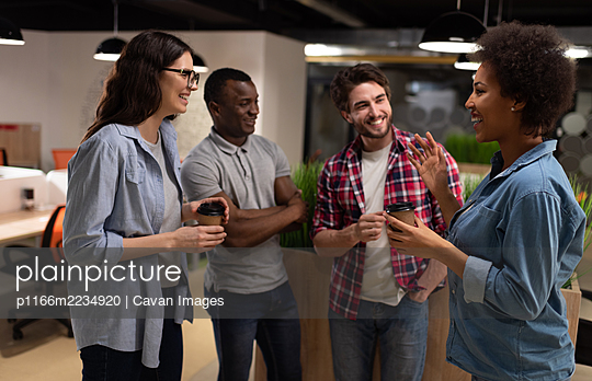 Cheerful black woman discussing project with colleagues during break - p1166m2234920 by Cavan Images