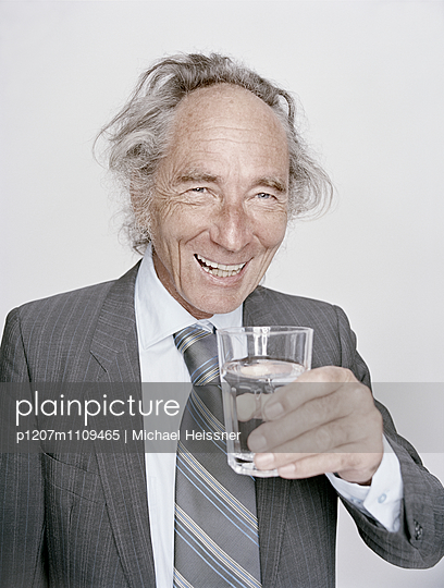 Senior businessman holding waterglass in hand - p1207m1109465 by Michael Heissner