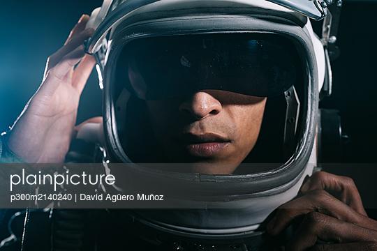 Man posing dressed as an astronaut in skyrocket elevator - p300m2140240 by David Agüero Muñoz