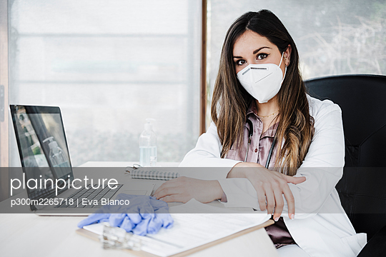 Female doctor with protective face mask sitting at desk in hospital during COVID-19 - p300m2265718 by Eva Blanco