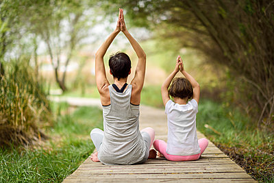 Rear view of mother and daughter doing yoga on boardwalk - p300m1587315 von Javier Sánchez Mingorance