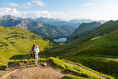 Germany, Bavaria, Oberstdorf, mother and little daughter on a hike in the mountains looking at view - p300m2028806 by Daniel Ingold