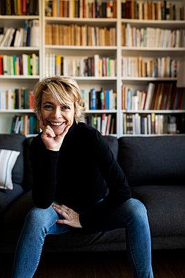 Portrait of happy mature woman sitting on couch at home - p300m2144803 von Valentina Barreto