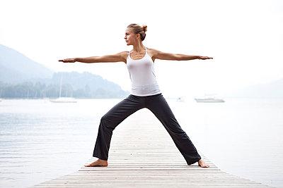 Junge Frau macht eine Yogaübung an einem See - p473m923092f von STOCK4B-RF