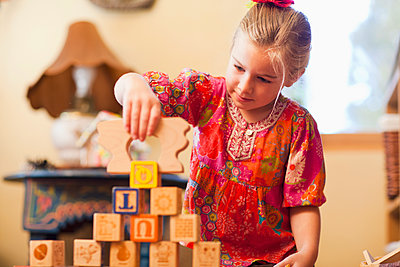 Caucasian girl stacking blocks - p555m1478220 by John Lund/Marc Romanelli