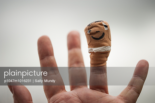 Plaster on a finger with a smiley face drawn on it - p1047m1016231 by Sally Mundy