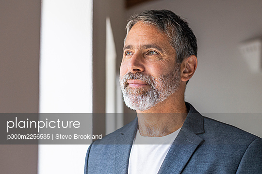Thoughtful businessman looking away while standing at home - p300m2256585 by Steve Brookland