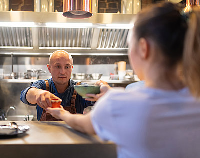 Cook giving food to waitress - p1166m2250622 by Cavan Images
