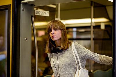 Junge Frau im Eingang der geöffnete Tür einer S-Bahn  - p1212m1136970 von harry + lidy
