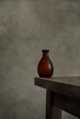 Old glass bottle on the corner of a table - p1228m1465513 by Benjamin Harte