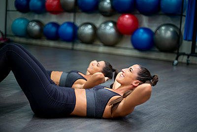 Twin sisters training in gym doing sit-ups - p300m2132321 von Oscar Carrascosa Martinez