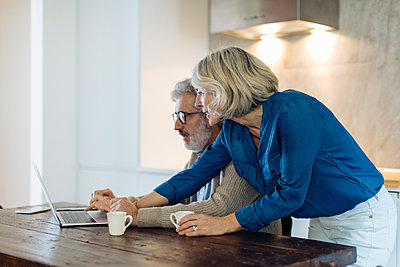 Mature man with wife using laptop on kitchen table at home - p300m2160342 by Sofie Delauw