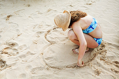 Girl making heart on sand - p312m1570700 by Anna Kern