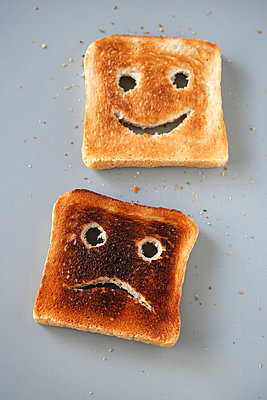 Two slices of toast - one with a smiling face, the other with a sad face - p450m1559167 by Hanka Steidle