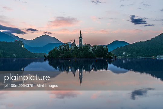 Village church and buildings reflected in still lake, Bled, Upper Carniola, Slovenia,Bled, Upper Carniola, Slovenia - p1100m2084375 by Mint Images