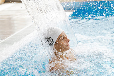 Young woman with swimming cap relaxing under a waterfall jet in a spa - p1166m2189705 by Cavan Images