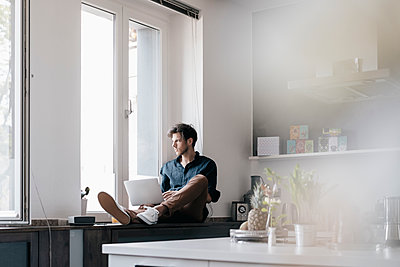 Young man with laptop sitting on window sill in a loft looking out of the window - p300m1549729 by Kniel Synnatzschke
