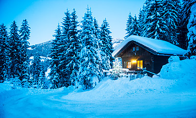 Austria, Altenmarkt-Zauchensee, sledges, snowman and Christmas tree at illuminated wooden house in snow at dusk - p300m2042029 by Hans Huber