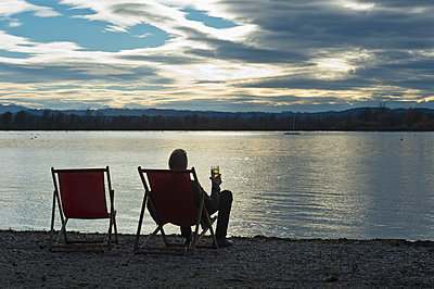 Germany, man sitting at lakeshore of Ammersee with glass of beer watching sunset - p300m2079280 by Claudia Rehm