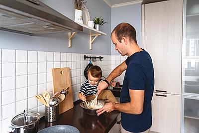 Moskau, Russland. Ein lachender glücklicher Mann mit dem Sohn bereit das Essen auf der Küche vor - p300m2277678 von Katharina und Ekaterina