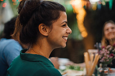 Smiling young woman looking away during dinner party in backyard - p426m2046203 by Maskot
