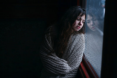 Sad Caucasian woman wrapped in scarf leaning on window - p555m1472993 by Dmitriy Bilous
