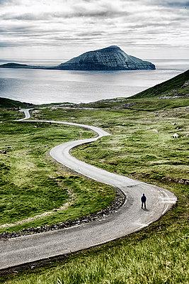 Stremnoy island, Faroe Islands, Denmark. Man standing on a bending road. (MR) - p651m2006831 by Marco Bottigelli