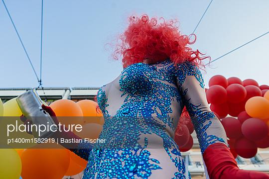 Eine Dragqueen mit roten Haaren in blauem Pailettenkleid vor bunten Luftballons - p1400m1582919 von Bastian Fischer