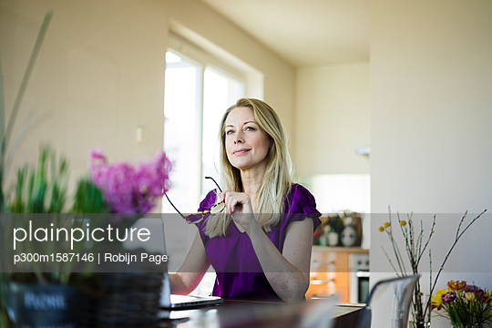 Portrait of businesswoman sitting at table using laptop at home - p300m1587146 von Robijn Page