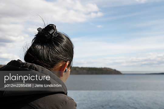 Woman with earphones at lake - p312m2285498 by Jens Lindström