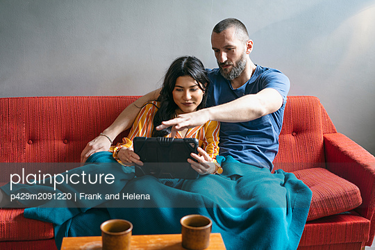Hipster couple using digital tablet on sofa - p429m2091220 by Frank and Helena