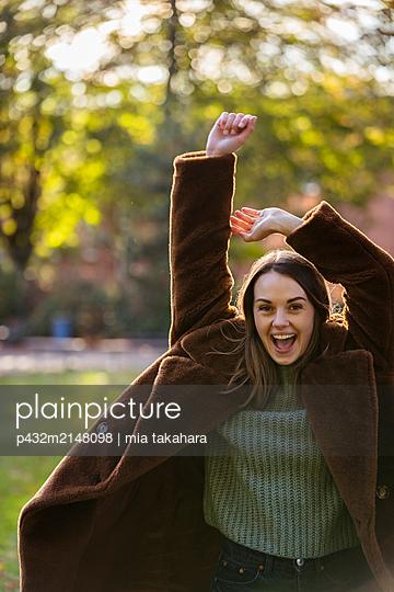Glückliche junge Frau im Park - p432m2148098 von mia takahara