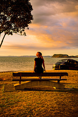 Woman on park bench at sunset - p1455m2204837 by Ingmar Wein