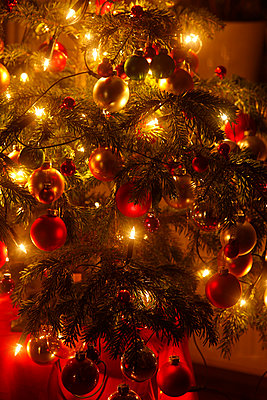Christmas tree with Christmas baubles and light chains, partial view - p300m2103220 by Thomas Jäger