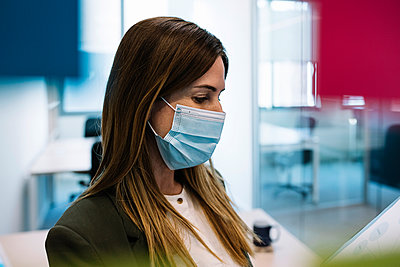 Businesswoman wearing protective face mask at office during COVID-19 - p300m2277751 by Xavier Lorenzo