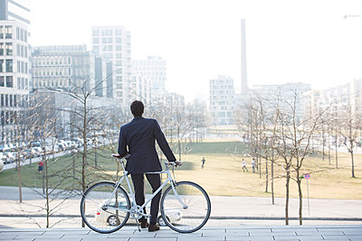 Businessman with bicycle taking a break in city - p1026m1139956 by Patrick Frost