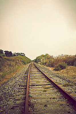 Single rail track leading into distance - p1047m789466 by Sally Mundy