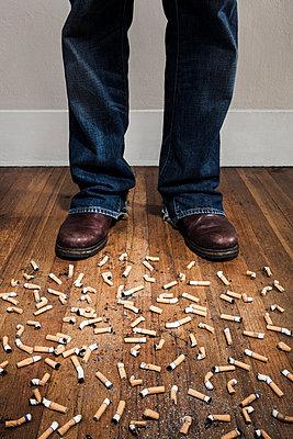 Mann vor Zigarettenkippen - p1094m900243 von Patrick Strattner