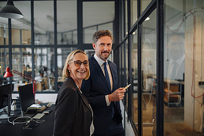 Smiling businessman and businesswoman standing at drawing on glass pane in office - p300m2156013 by Gustafsson