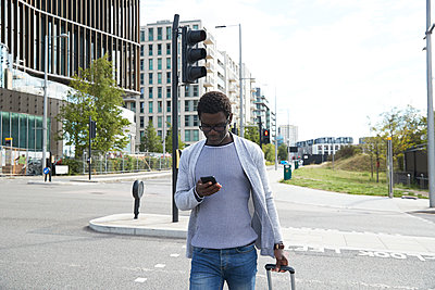 Male entrepreneur using mobile phone while walking on street in city - p300m2241048 von Pete Muller