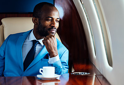 Elegant businessman with hand on chin looking though window in private jet - p300m2256367 by OneInchPunch