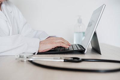 Senior female doctor working on digital tablet at desk in hospital - p300m2273977 by Eva Blanco