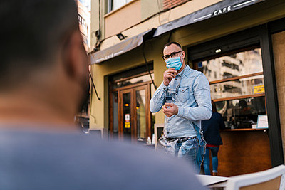 Waiter with protective face mask talking to customer - p300m2274282 by Ezequiel Giménez