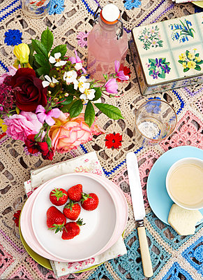Strawberries and pink lemonade with cut flowers on crochet tablecloth in Isle of Wight home;  UK - p349m920067 by Rachel Whiting