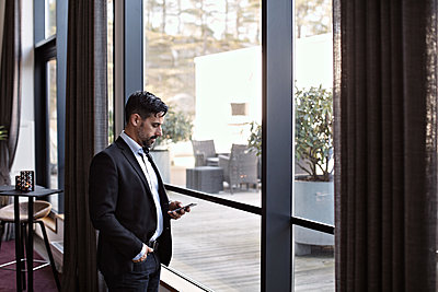 Businessman using phone while standing by window in office - p426m2117035 by Maskot
