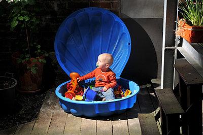 Kleinkind spielt in einem Plastiksandkasten - p446m1119692 von Jan Knoff