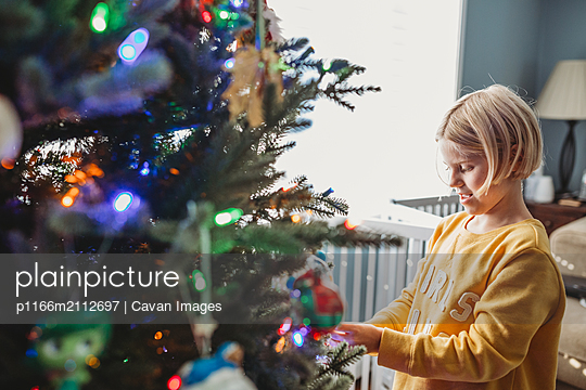 Girl decorating Christmas Tree with colored lights - p1166m2112697 by Cavan Images