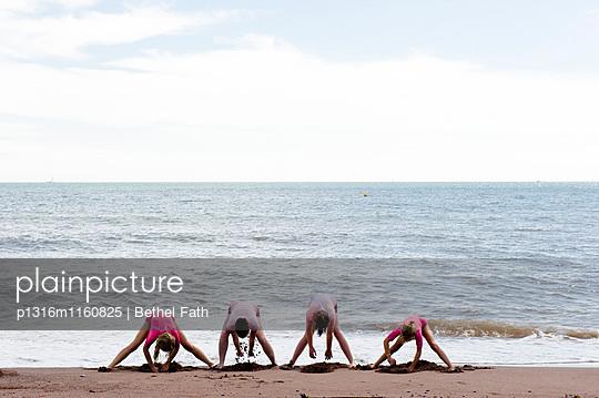 Vier Personen buddeln am Strand, Teignmouth, Devon, South West England, England, Großbritannien - p1316m1160825 von Bethel Fath
