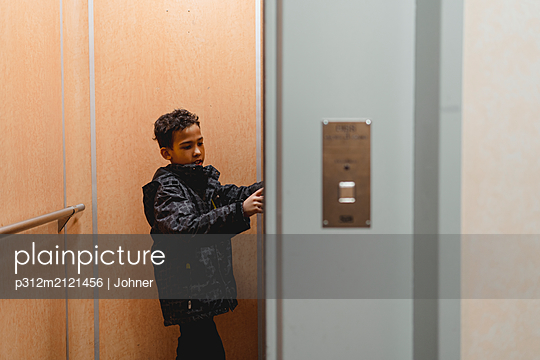 Boy in lift - p312m2121456 by Johner